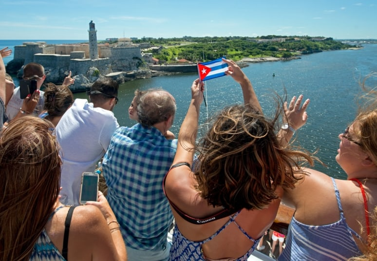Lynette Papapanos, second from right, displays a Cuban flag as she and other passengers aboard the Carnival Paradise pass the El Morro Castle in Havana, Cuba, Friday, June 30, 2017. The arrival marked the first time a Carnival Cruise Line ship has ported in Cuba and heralded the beginning of a series of a dozen Tampa, Fla.,-to-Cuba cruises scheduled for the ship through May 3, 2018. About 2,400 passengers are aboard the 855-foot-long vessel for the inaugural voyage. Papapanos is a Tampa resident. FOR EDITORIAL USE (Andy Newman/Carnival Cruise Line/HO)